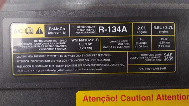 Foto de uma etiqueta - Ford Edge 2011 - indicando fluido refrigerante R-134a, sua quantidade de fluido específica para cada tipo de motor, e seu tipo de óleo lubrificante e quantidade total específica