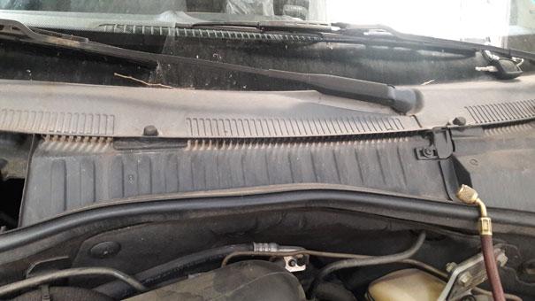 Foto de localização do sistema de filtro de cabine de um Corsa Hatch: filtro localizado abaixo do para-brisa, entre o isolamento do cofre do motor e o sistema de limpador do para-brisa