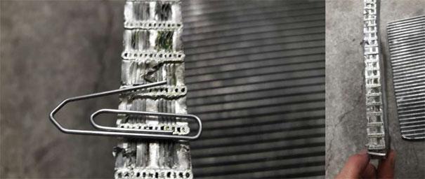 """Foto de comparação. Cortamos o condensador moderno de modelo """"microfuros"""" chamados de """"fluxo paralelo"""", para termos noções da espessura da passagem do fluido refrigerante no condensador ao lado de um clipe, e ainda para ilustrar o motivo de fácil obstrução do mesmo. Em alguns modelos não conseguimos realizar a limpeza adequada do sistema com o produto especial R-141b no condensador, recomendando a sua substituição"""