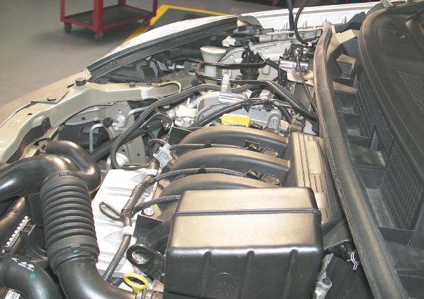 O motor, visto de lado: em primeiro plano a tubulação do coletor de ar; o filtro fica escondido atrás da caixa